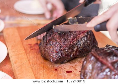 Cutting fried beef in the kitchen in restaurant