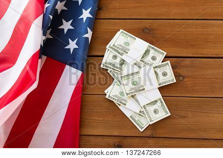 state budget, finance and nationalism concept - close up of american flag and dollar cash money on wood