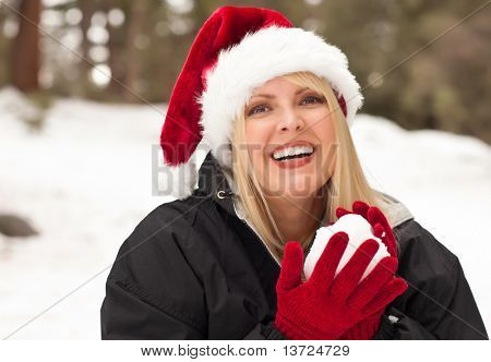 Attractive Santa Hat Wearing Blond Woman Having Fun in The Snow on a Winter Day.