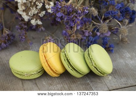 French dessert macarons with flower. Almond cookies.