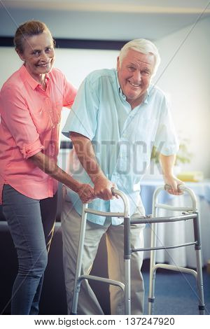 Portrait of happy senior woman helping senior man to walk with walker
