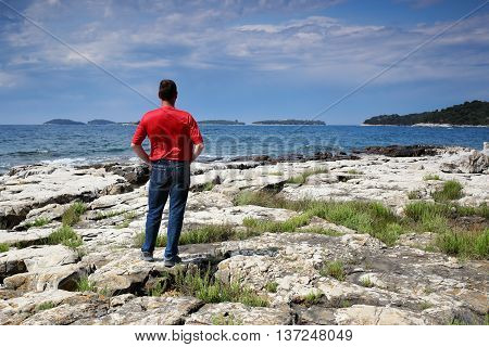 man is looking to islands in ocean