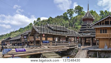 Zhaoxing Dong Village Guizhou Province China - April 8 2010: Panoramic view to the village ethnic minorities wooden covered bridge and drum tower next to wooden huts near rural river spring.