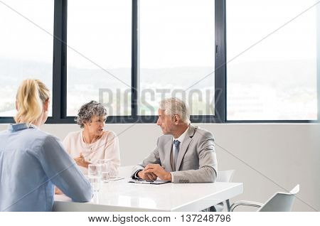 Business executive conducting job interview with young woman. Personnel managers conducting job interview talking about their decision. Team of human resources conducting interviews at office.