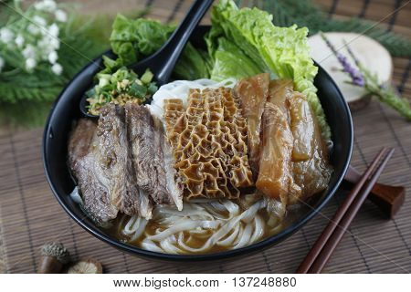 Chinese bowl of vermicelli noodle with fried beef cow's stomach and salad on the table