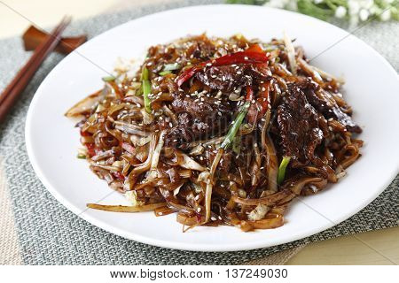 Traditional chinese plate of mixed vermicelli with beef on the table in restaurant