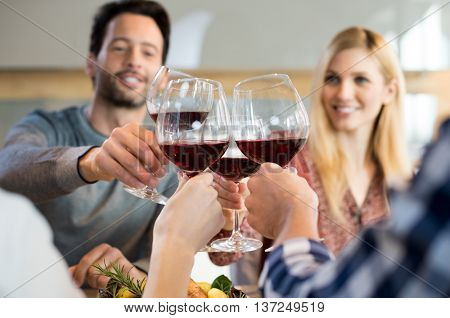 Close up of people cheering with red wine while sitting at dining table. Friends raising their glasses in a toast in a restaurant. Friends having lunch together.