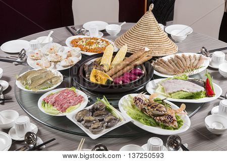 Traditional chinese tray food of seafood produce beef and pork on the table in restaurant