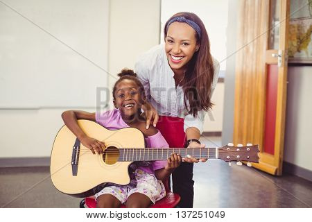 Teacher assisting a girl to play a guitar in classroom at school