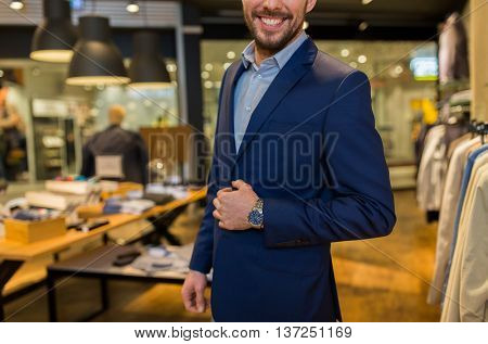 sale, shopping, fashion, style and people concept - close up of happy man in suit at clothing store