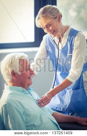 Female doctor checking heartbeat of senior man at home