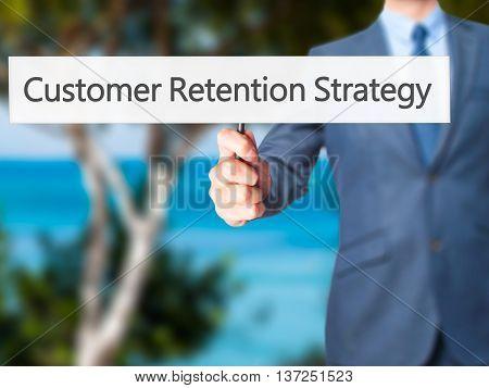 Customer Retention Strategy - Businessman Hand Holding Sign