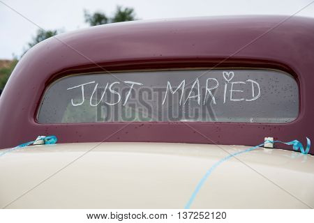 Just Married Written On The Trunk Of A Red Car