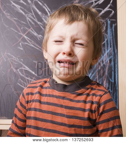 little cute boy screaming and crying at school near blackboard close up, punished children concept