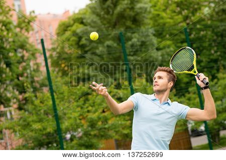 Skillful male tennis player is beating off a ball. He is standing and raising a racket. Man is looking at ball with concentration