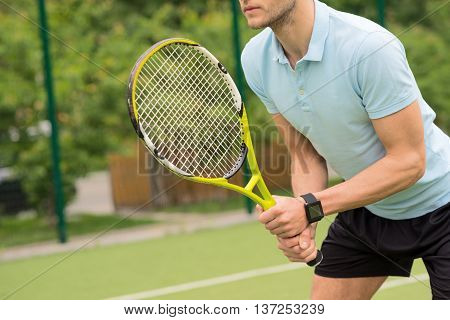 Skillful male tennis player is preparing to beat a ball. He is holding a racket and posing. Man is standing on tennis court