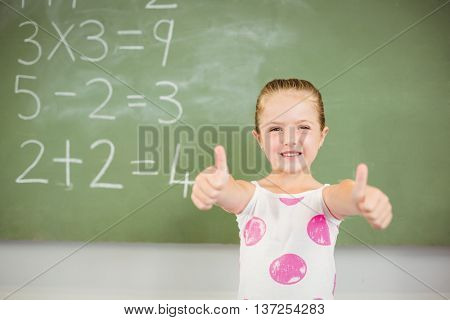 Portrait of smiling schoolgirl showing thumbs up in classroom at school