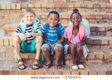 Portrait of smiling school kids sitting together on stairs at school