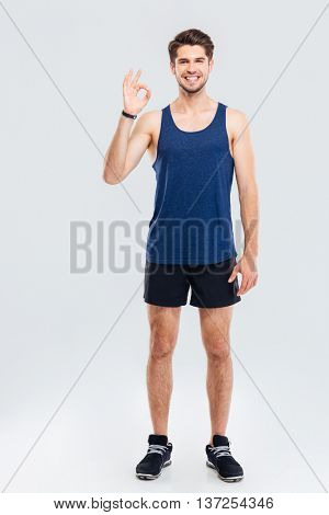 Full length portrait of a fitness man showing okay sign isolated on a gray background