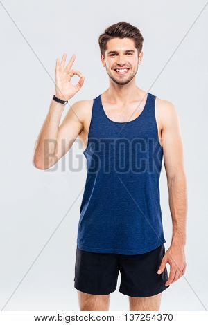 Close-up portrait of a fitness man showing okay sign isolated on a gray background