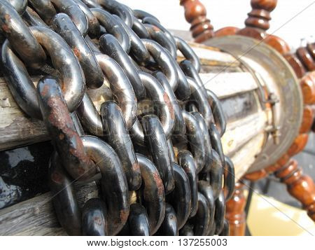 old historical helm with rusty chain control