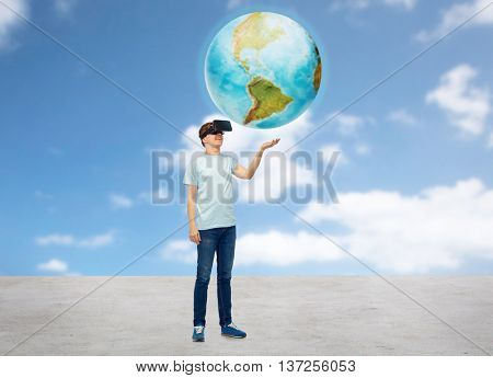 3d technology, virtual reality, entertainment, cyberspace and people concept - happy man with virtual reality headset or 3d glasses playing game and holding earth globe over sky and clouds background
