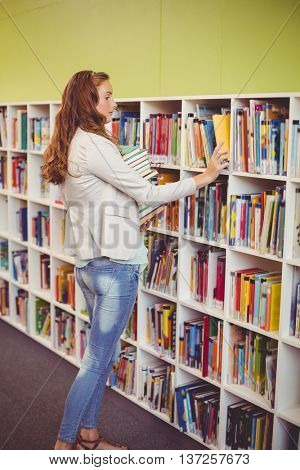 School teacher selecting a book from bookcase in library at school