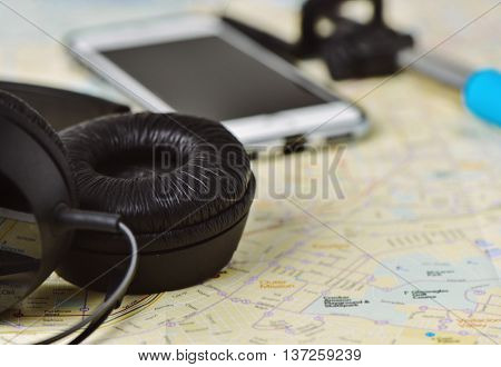 closeup of a pair of headphones, a smartphone and a selfie stick on a city map