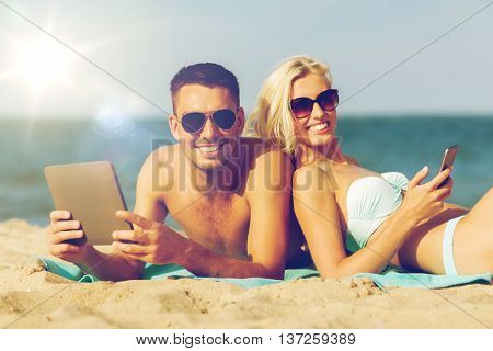 love, travel, tourism, technology and people concept - happy couple on vacation with tablet pc computer sunbathing on summer beach