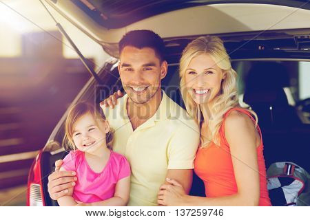 transport, leisure, road trip and people concept - happy family with little girl sittin on open hatchback car  trunk at home parking space