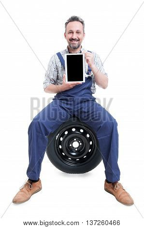 Handsome Mechanic Sitting On Tire And Showing Tablet