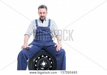Serious Mechanic With Spanner Sitting On Car Tire