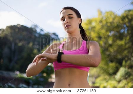 Beautiful woman adjusting a time on wristwatch in park