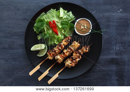 Chicken Satay or Sate Ayam - Malaysian famous food. Satay, modern Indonesian and Malay spelling of sate, is a dish of seasoned, skewered and grilled meat, served with a peanut sauce. Top view