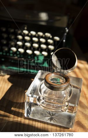 An antique crystal inkwell and a typewriter