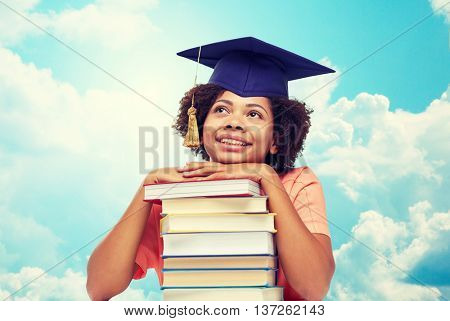education, school, knowledge and people concept - happy smiling african american student girl in bachelor cap with books sitting at table and dreaming over blue sky and clouds background