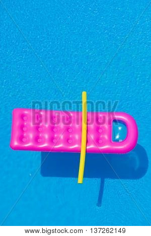 Pink air bed and yellow tube floating on a swimming pool