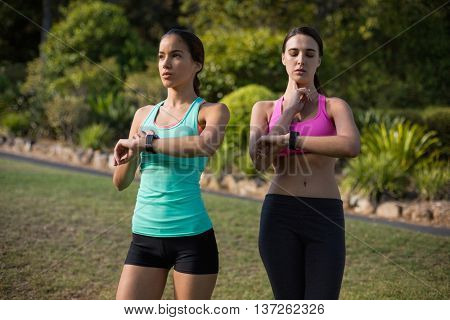 Beautiful women checking a time on wristwatch in park