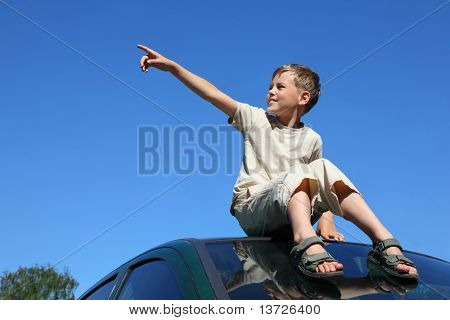 Boy sits on  roof of car, shows  hand and looks aside