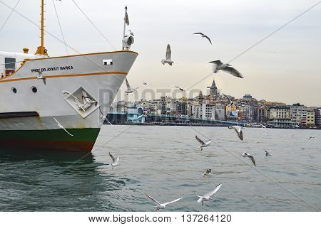 Istanbul Turkey - February 21 2013: Istanbul Strait ferry and seagulls. Gulls to feed the passion of ferry passengers. Galata bridge and Galata tower in the background.