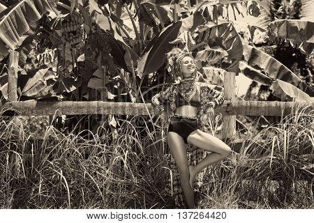 Attractive young boho woman in turban at jungle background