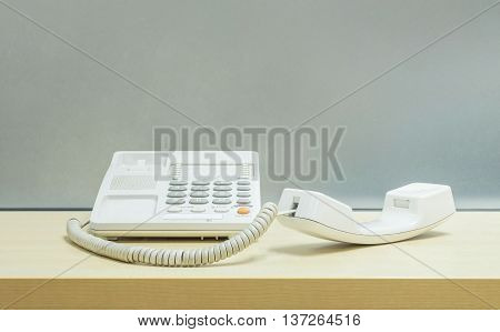 Closeup white phone office phone on blurred wooden desk and frosted glass wall textured background in the work office