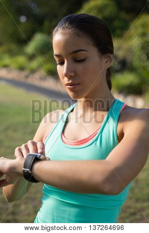 Woman adjusting a time on wristwatch in park