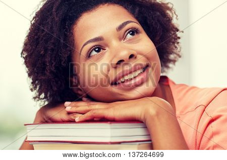 education, school, knowledge and people concept - happy smiling african american student girl with books sitting at table and dreaming at home