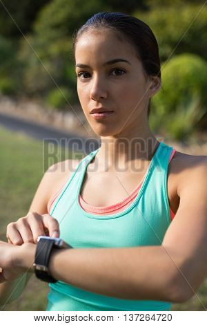 Portrait of woman adjusting a time on wristwatch in park