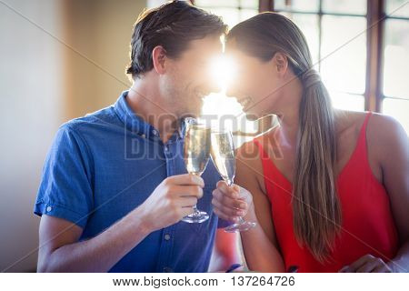 Young couple looking face to face and toasting champagne flutes in a restaurant