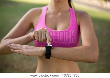 Mid section of woman adjusting a time on wristwatch in park