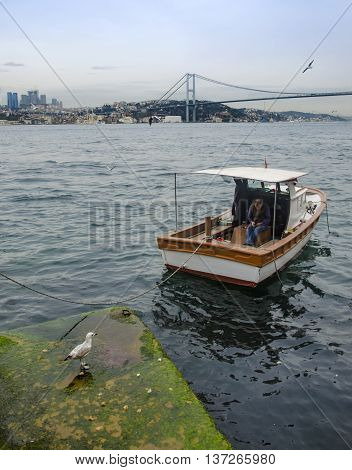 Istanbul Turkey - March 28 2015: Istanbul Bosphorus views And Uskudar Kuzguncuk coast a man resting on the boat. Istanbul Bosphorus Bridge in the background looks. The European part of Istanbul is seen along the coast towards the throat.
