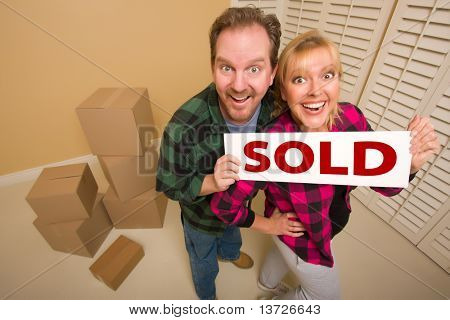 Goofy Couple Holding Sold Sign in Room Surrounded by Cardboard Boxes.