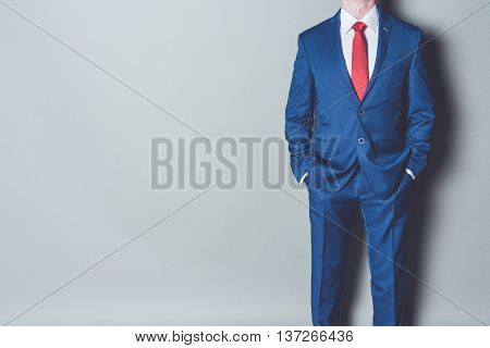 Portrait of successful businessman wearing blue siut and red tie against gray background